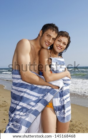 Portrait of happy young couple wrapped in towel standing at beach