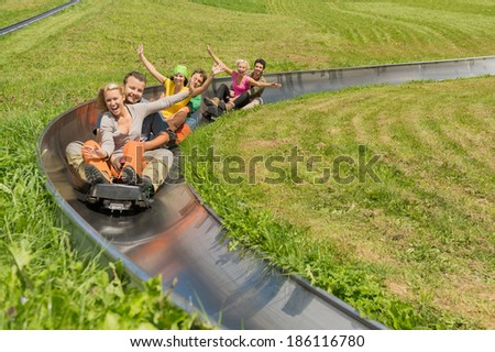 Portrait of happy young couples enjoying summer sledge ride - stock photo