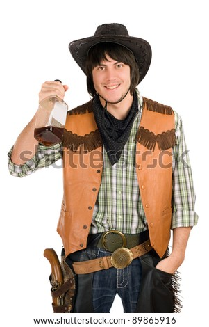 Portrait of happy young cowboy with a bottle of whiskey in hand - stock photo