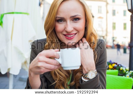 Portrait of happy young cute elegant woman sitting outdoor in a cafe with cup of coffee in a city - stock photo