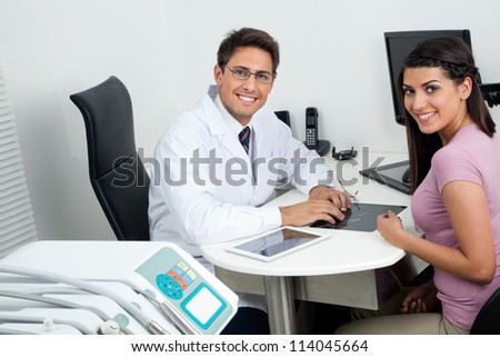 Portrait of happy young dentist and female patient sitting at office desk