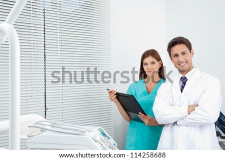 Portrait of happy young doctor and female assistant with clipboard in dental clinic - stock photo