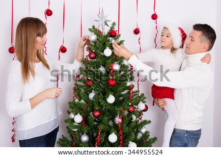 portrait of happy young family decorating Christmas tree - stock photo
