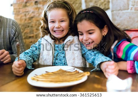 Portrait of happy young family having breakfast in the cafe.