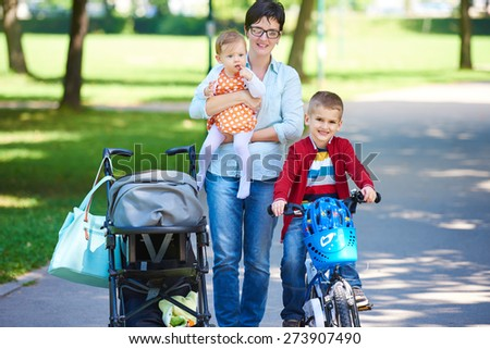 portrait of happy young family,  mother and  kids have fun in park - stock photo