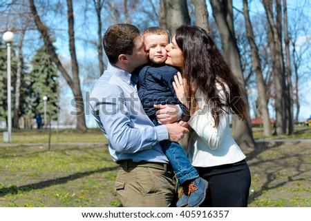 Portrait of happy young family spending time together in green nature in park. Mother, father and son having fun outdoors on a spring sunny day. Concept of happy family life, love and happiness.