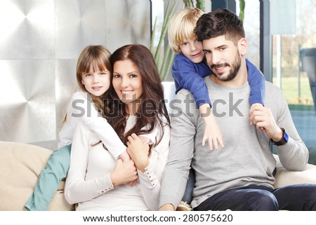 Portrait of happy young family with two kids sitting at sofa and smiling. Happy father giving piggyback to his cute son.  - stock photo