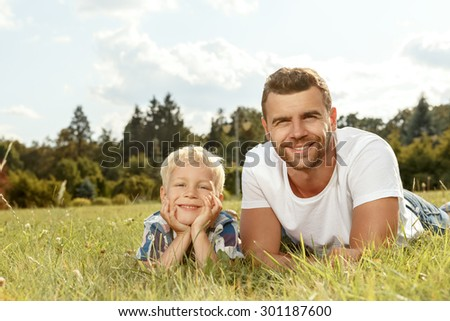 Portrait of happy young father and son in the park - stock photo