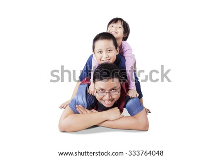 Portrait of happy young father playing with his children in the studio while lying on the floor, isolated on white background - stock photo