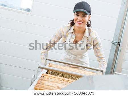 Portrait of happy young female beekeeper working in beekeeping factory