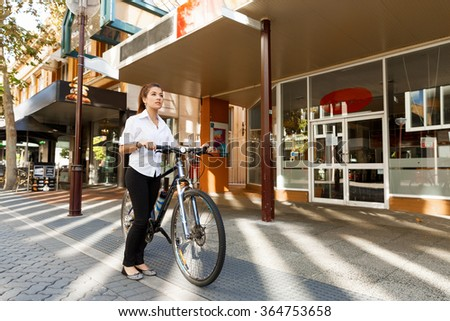 Portrait of happy young female bicyclist - stock photo