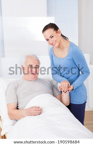 Portrait of happy young female caregiver with senior man in nursing home - stock photo