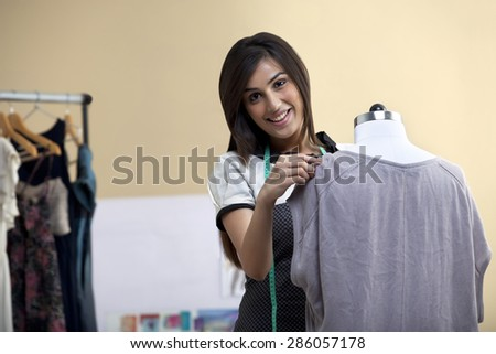Portrait of happy young female designer fixing dress on mannequin - stock photo