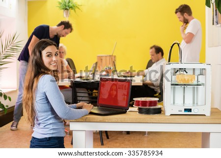 Portrait of happy young female designer using laptop by 3D printer with colleagues in background at studio - stock photo