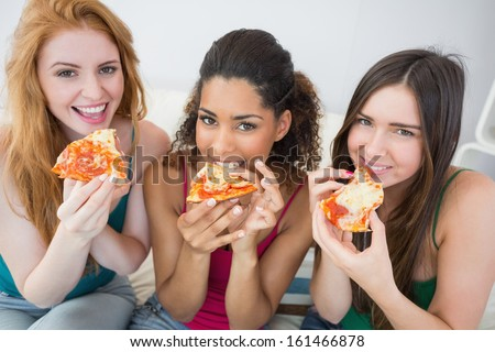 Portrait of happy young female friends eating pizza on sofa at home - stock photo