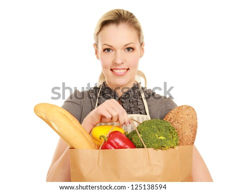 Portrait of happy young female holding a shopping bag full of groceries on white background