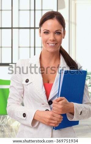 Portrait of happy young female officeworker holding folder in colorful setting.