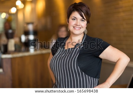 Portrait of happy young female owner with hands on hips standing in coffee shop - stock photo