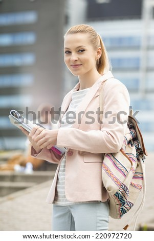 Portrait of happy young female student at college campus - stock photo