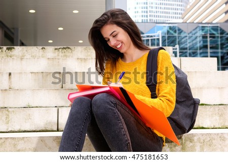 Portrait of happy young female student taking notes on steps