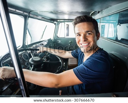 Portrait of happy young fireman driving firetruck at station - stock photo