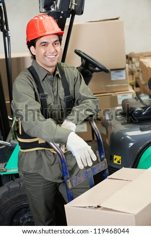 Portrait of happy young foreman leaning on handtruck at warehouse - stock photo