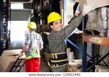 Portrait of happy young foreman lifting cardboard box with coworker pushing handtruck at warehouse - stock photo