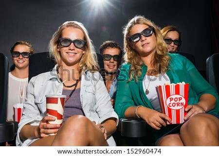 Portrait of happy young friends with popcorn and soda watching 3D movie in theater