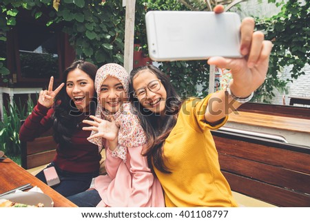 portrait of happy young girl friend taking selfie together in cafe