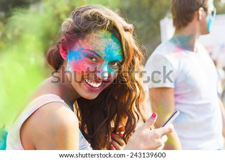 Portrait of happy young girl on holi color festival using mobile phone - stock photo