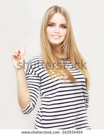 Portrait of happy young girl raising her arms and showing victory sign - stock photo