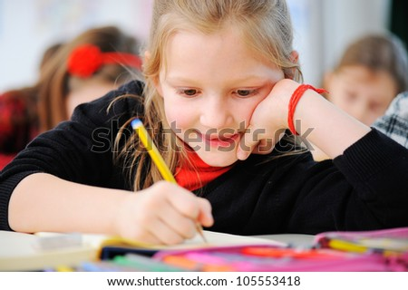 Portrait of happy young girls writing notes in school classroom with friends in background - stock photo