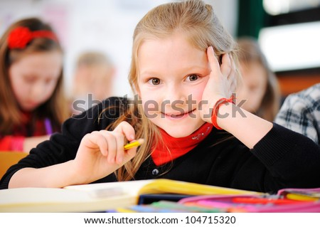 Portrait of happy young girls writing notes with friends in background - stock photo