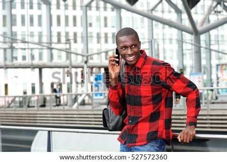Portrait of happy young guy at railway station using cell phone