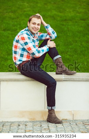 Portrait of happy young happy man relaxing near green lawn in the park and checking time. Trendy casual clothing and leather boots. Perfect smile. Copy-space. Outdoor shot - stock photo