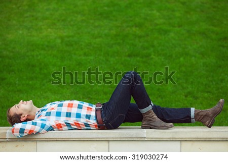 Portrait of happy young happy man relaxing near green lawn in the park, smiling and looking up in the sky. Trendy casual clothing and leather boots. Perfect smile. Copy-space. Outdoor shot - stock photo