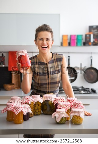 Portrait of happy young housewife among jars with homemade fruits jam and pickled vegetables - stock photo