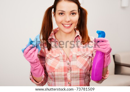 portrait of happy young housewife doing the household chores - stock photo