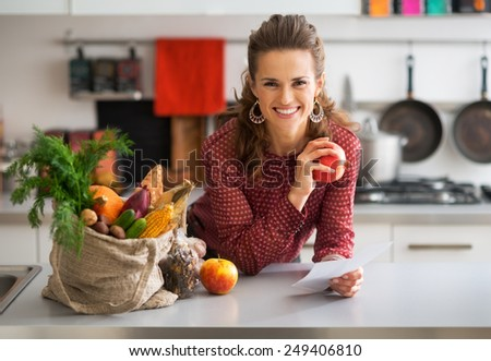 Portrait of happy young housewife holding grocery shopping checks in kitchen - stock photo