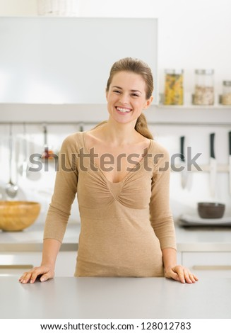 Portrait of happy young housewife in modern kitchen