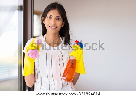 portrait of happy young indian woman doing housework - stock photo