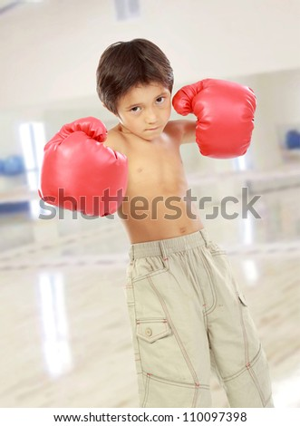 portrait of happy young kid with boxing glove ready to fight in the gym - stock photo