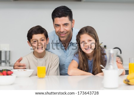 Portrait of happy young kids enjoying breakfast with father in the kitchen
