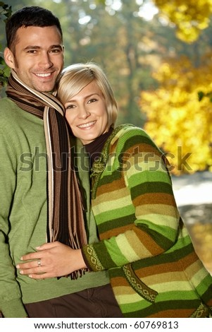 Portrait of happy young love couple in autumn park looking at camera, smiling.?