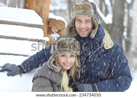 Portrait of happy young loving couple smiling at wintertime in snowfall. - stock photo