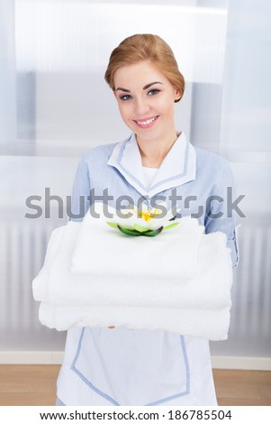 Portrait Of Happy Young Maid Holding Towels - stock photo