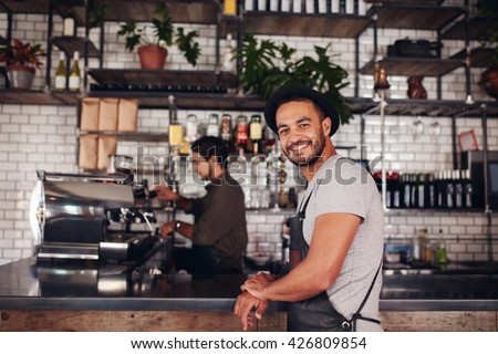 Portrait of happy young male coffee shop owner standing with barista working behind the counter making drinks. - stock photo