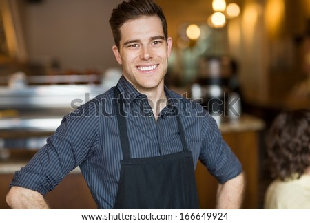 Portrait of happy young male owner standing in cafe - stock photo