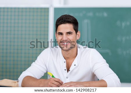 Portrait of happy young male student in classroom