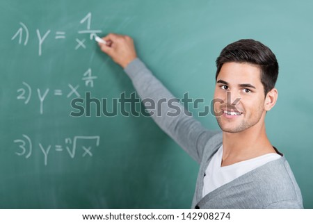 Portrait of happy young male student solving sums on chalkboard in classroom - stock photo
